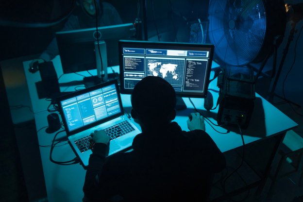 man at two computers in dark room